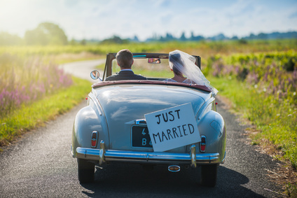 A newlywed couple is driving a retro car, rear view